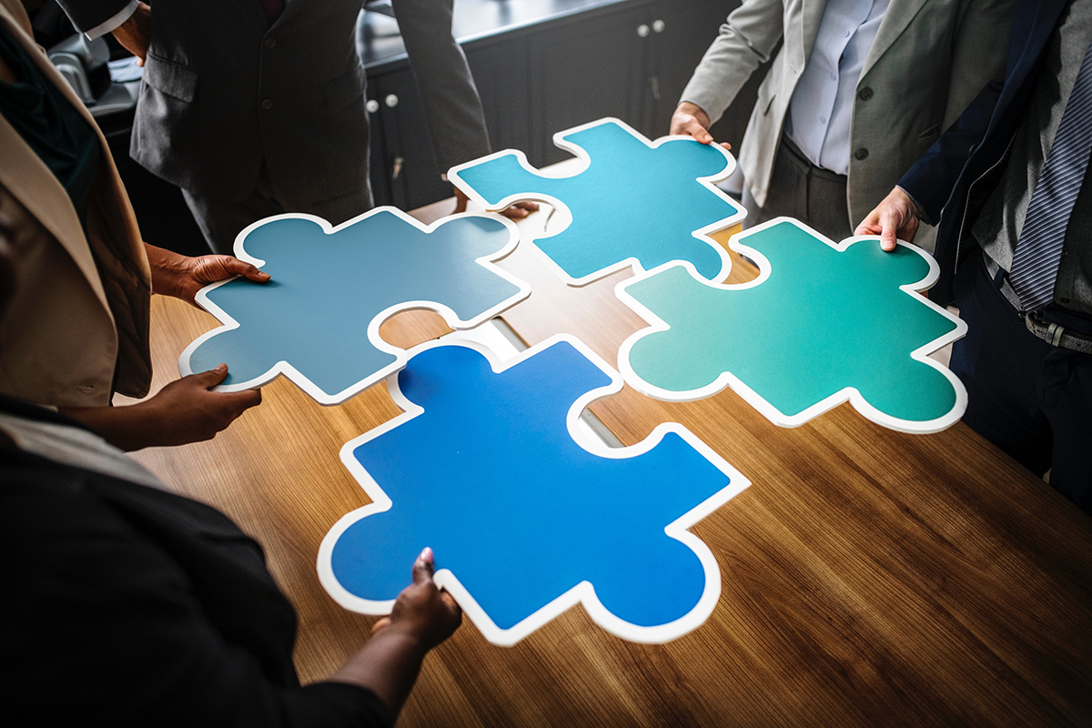 People holding oversize puzzle pieces over conference table